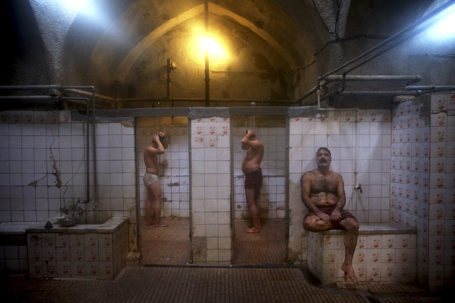 In this January 9, 2015 photo, patrons shower at the Ghebleh public bathhouse, in Tehran, Iran. (Photo by Ebrahim Noroozi/AP Photo)