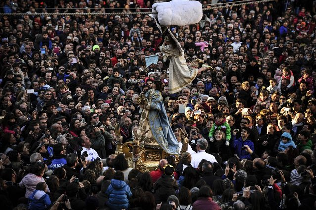 """Eight-year-old Alba Oroz, secured by a harness, is transported in the air, above the crowd as she unveils the face of a statue of the Virgin Mary, during the Easter Sunday ceremony """"Descent of the Angel"""", during Holy Week in the small town of Tudela, northern Spain, Sunday, April 5, 2015. (Photo by Alvaro Barrientos/AP Photo)"""