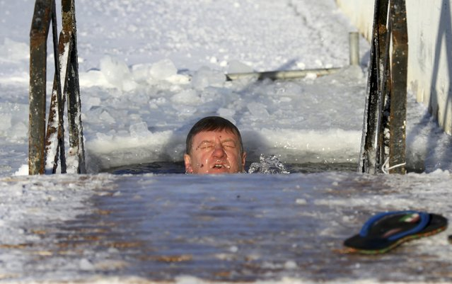 A man takes a dip in icy waters as the temperature dropped to around minus 26 degrees Celsius (minus 14.8 degrees Fahrenheit) in Minsk, Belarus January 7, 2017. (Photo by Vasily Fedosenko/Reuters)