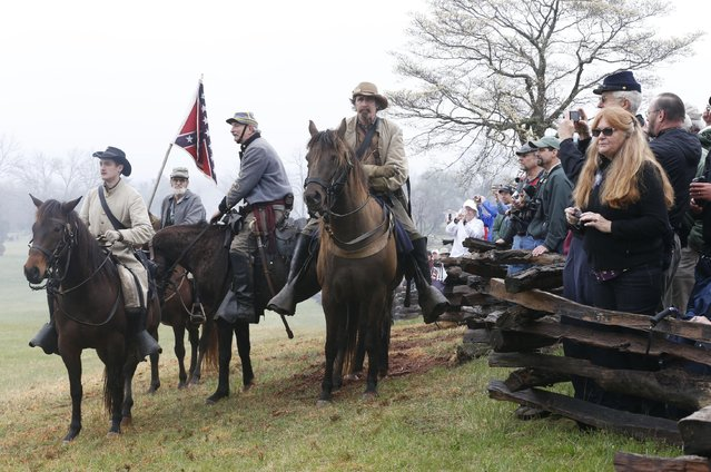 Confederate officers watch the battle during a re-enactment of the Battle of Appomattox Courthouse as part of the commemoration of the 150th anniversary of the surrender of the army of Northern Virginia at Appomattox Court House in Appomattox, Va., Thursday, April 9, 2015. (Photo by Steve Helber/AP Photo)