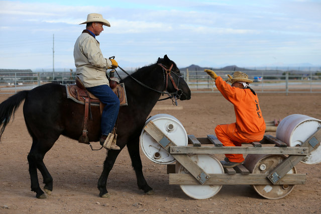 Randy Helm rides a horse, while inmate Gabriel Curtis gestures, as they train a horse as part of the Wild Horse Inmate Program (WHIP) at Florence State Prison in Florence, Arizona, U.S., December 2, 2016. (Photo by Mike Blake/Reuters)