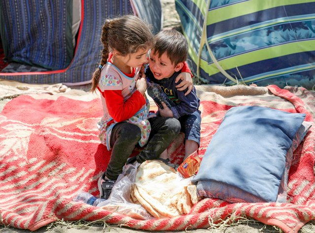An internally displaced boy from northern provinces, who fled from his home due the fighting between Taliban and Afghan security forces, is comforted by his sister in a public park that they use as shelter in Kabul, Afghanistan, August 10, 2021. (Photo by Reuters/Stringer)