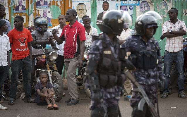 Ugandan riot police stand close to dejected opposition supporters to prevent them from demonstrating, shortly after the election result was announced, in downtown Kampala, Uganda, aturday, February 20, 2016. (Photo by Ben Curtis/AP Photo)