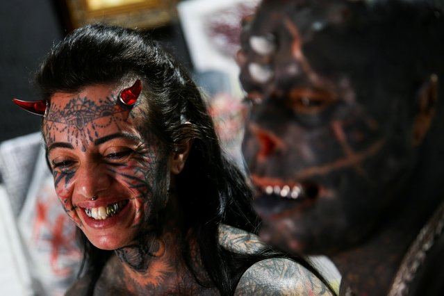Brazilian tattoo artist Michel Praddo, also known as Diabao or Human Satan, and his wife Carol Praddo, known as Mulher Demonia or Demon Woman, laugh as they talk about body modifications in their studio in Praia Grande, Brazil August 18, 2021 on August 18, 2021. (Photo by Carla Carniel/Reuters)