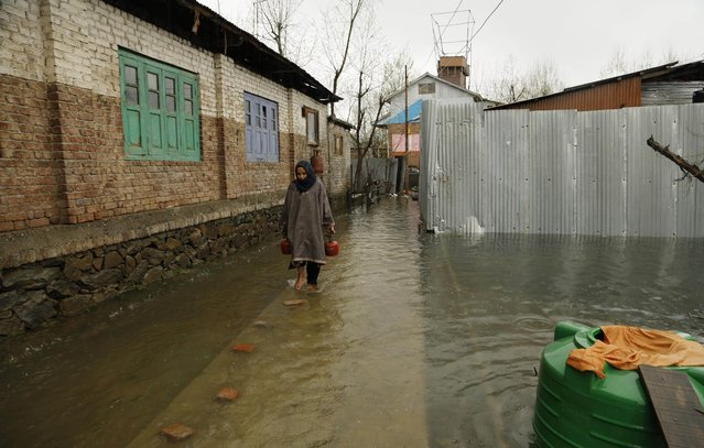A Kashmiri woman carries household goods to a safer area after flood waters surrounded her home in Srinagar, India, Wednesday, April 1, 2015. (Photo by Mukhtar Khan/AP Photo)