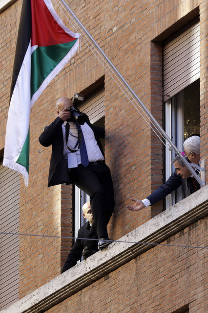 A photographer leans out of a window to take pictures of Palestinian President Mahmoud Abbas, right, inside the newly inaugurated Palestinian embassy to the Holy See at the Vatican, Saturday, January 14, 2017. (Photo by Andrew Medichini/AP Photo)