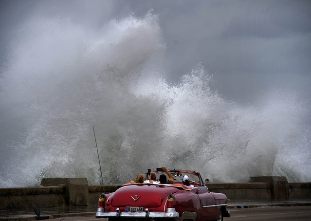 Waves crash against the Malecon, triggered by the outer bands of Hurricane Michael, as tourists drive past in a classic American car in Havana, Cuba, Tuesday, October 9, 2018. A fast and furious Hurricane Michael is churning toward the Florida Panhandle with 110 mph winds and a potential storm surge of 12 feet, giving tens of thousands of people precious little time to get out. (Photo by Ramon Espinosa/AP Photo)
