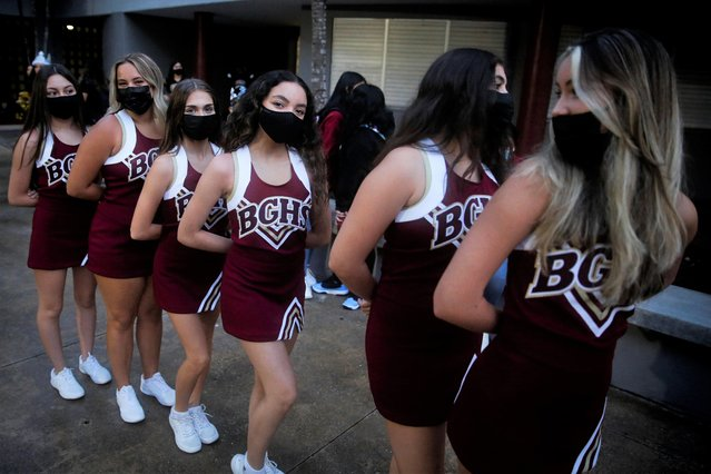 School cheerleaders wearing protective masks pose for a photo as fellow students arrive for classes on the first day of school in Miami-Dade County at Barbara Goleman Senior High School, in Miami, Florida, August 23, 2021. (Photo by Marco Bello/Reuters)