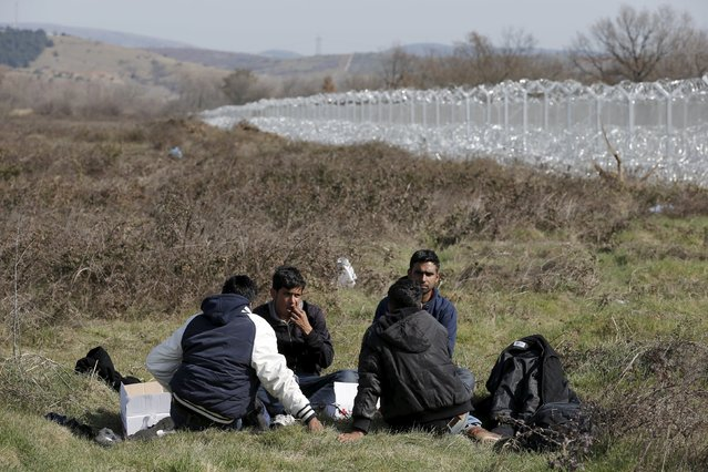 Migrants from Afghanistan take a rest on a field next to a border fence at the Macedonian-Greek border in Gevgelija, Macedonia February 23, 2016. (Photo by Marko Djurica/Reuters)