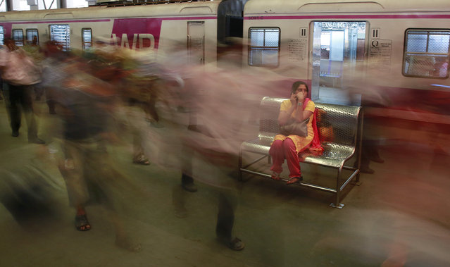 A woman waits as Indian commuters get off from trains at the Church Gate railway station in Mumbai, India, Thursday, February 25, 2016. (Photo by Rafiq Maqbool/AP Photo)