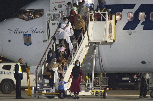 Afghan citizens evacuated by Romanian authorities from Afghanistan disembark an airplane at the Baza 90 military base after being flown in from Pakistan in Otopeni, near Bucharest, Romania, Thursday, September 9, 2021. The Romanian Foreign Ministry organized the evacuation of 156 Afghan citizens, former aides of the Romanian military that operated in Afghanistan, students, human rights activists, journalists, magistrates and their family members, of which 139 arrived to Romania on Thursday night. (Photo by Alexandru Dobre/AP Photo)