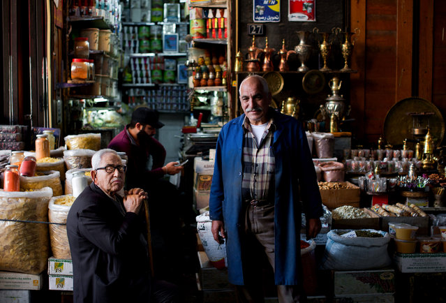 Syrian shopkeepers pose for a picture as they wait for customers at the popular Souk Tawil old market in Damascus, Syria, Wednesday, February 24, 2016. (Photo by Hassan Ammar/AP Photo)