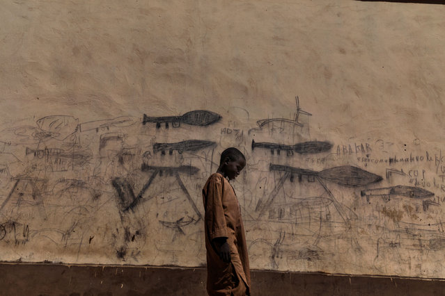 "Photo of the year nominee: Almajiri Boy, by Marco Gualazzini. An orphaned boy walks past drawings on a wall depicting rocket-propelled grenade launchers, in Bol, Chad. This image was also nominated as part of a set in the ""photo story of the year"" and ""environment story"" categories. (Photo by Marco Gualazzini/Contrasto/World Press Photo 2019)"