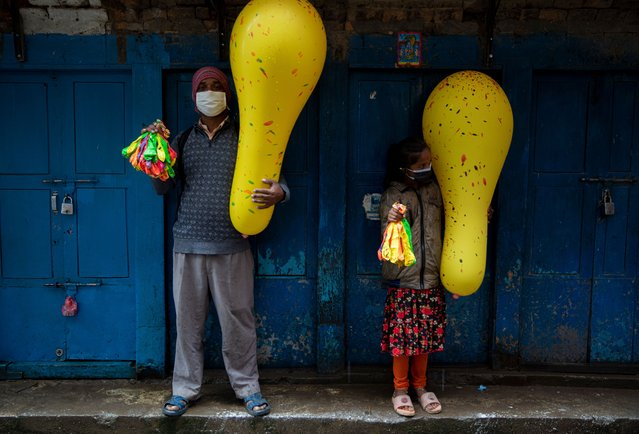 Father and daughter sell balloons during the Gai Jatra (Cow Festival) procession held amid the coronavirus pandemic, in Kathmandu, Nepal, 23 August 2021. Nepalese Hindus celebrate the religious festival to ask for salvation and peace for their family members who have passed away in the past year. Children participating in the procession often dress as cows, holy animals according to Hindu belief, who help departed souls to reach heaven. (Photo by Narendra Shrestha/EPA/EFE)