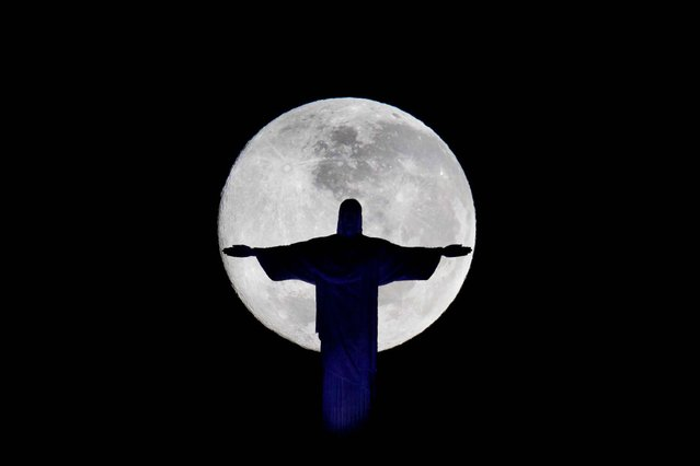 A full moon is seen behind the Christ the Redeemer statue on July 4, 2012. (Photo by Felipe Dana/Associated Press)