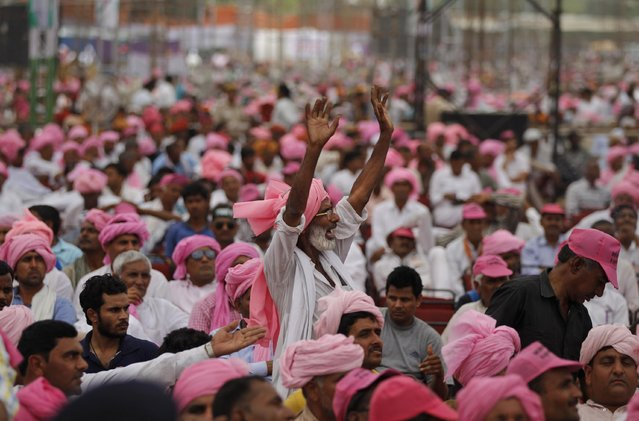 An Indian farmer shouts slogans in support as India's opposition Congress party vice president Rahul Gandhi addresses them during a rally against land bill in New Delhi, India, Sunday, April 19, 2015. Tens of thousands of flag-waving farmers rallied in India's capital on Sunday to protest the government's plan to ease rules for obtaining land for industry and development projects. (Photo by Altaf Qadri/AP Photo)