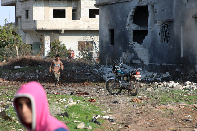 Boys are seen near a damaged house after a strike on rebel-held Tafas town, in Deraa Governorate, Syria January 22, 2017. (Photo by Alaa Al-Faqir/Reuters)