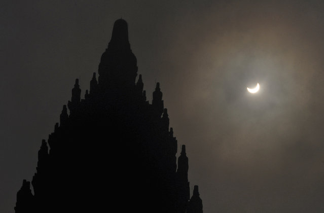 A partial solar eclipse is seen behind the 9th century Prambanan Temple in Yogyakarta, Indonesia, Wednesday, March 9, 2016. (Photo by Slamet Riyadi/AP Photo)