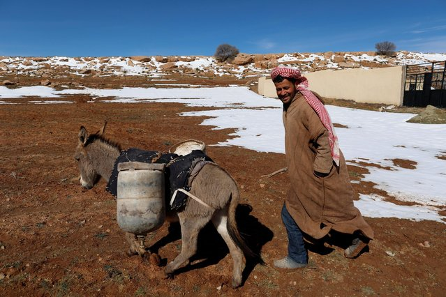 A man smiles as he walks beside his donkey carrying cans of gas butane on the outskirts of  Laghouat in the Saharian Atlas Mountains, Algeria January 26, 2017. (Photo by Zohra Bensemra/Reuters)