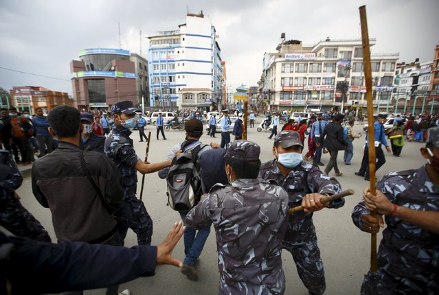 Nepalese police personnel try to stop earthquake victims from blocking traffic along a road as they protest against the government's lack of aid provided to the victims in Kathmandu, Nepal April 29, 2015. (Photo by Navesh Chitrakar/Reuters)