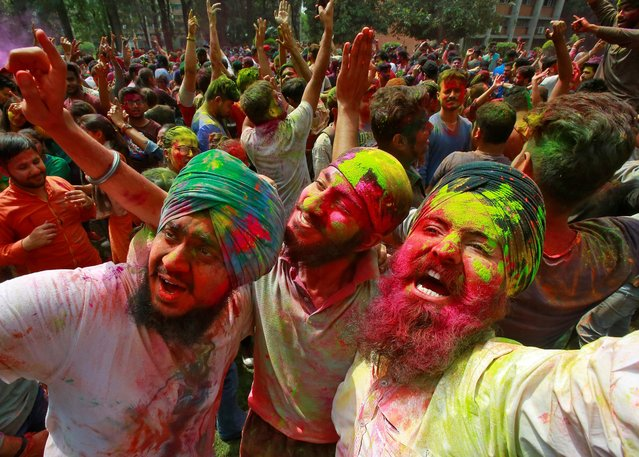 Students with their faces smeared in coloured powder dance as they celebrate Holi at a university campus in Chandigarh, India, March 20, 2019. (Photo by Ajay Verma/Reuters)