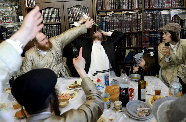 An ultra-Orthodox Jewish man drinks wine during Purim, a celebration of the Jews' salvation from genocide in ancient Persia, as recounted in the Book of Esther, in Jerusalem's Mea Shearim neighbourhood, March 22, 2019. (Photo by Ammar Awad/Reuters)