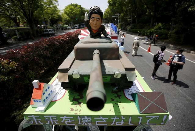 A protesters' float featuring Japan's Prime Minister Shinzo Abe riding a battle tank is seen during an annual May Day rally and march organized by the Group of the National Confederation of Trade Unions, commonly known in Japanese as Zenroren, in Tokyo May 1, 2015. Thousands of union workers and activists gathered and marched central Tokyo on International Workers' Day. (Photo by Issei Kato/Reuters)