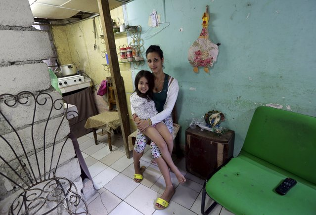 Jennifer, 24, and her daugther Yohane, 5, sit in their house in Havana February 28, 2016. (Photo by Enrique de la Osa/Reuters)