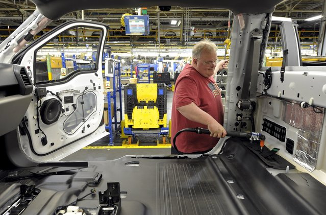 Auto worker Christopher Brower screws a component into the cab of a four-door F150 at Ford's Kansas City Assembly Plant where new aluminum intensive Ford F-Series pickups are built in Claycomo, Missouri May 5, 2015. (Photo by Dave Kaup/Reuters)