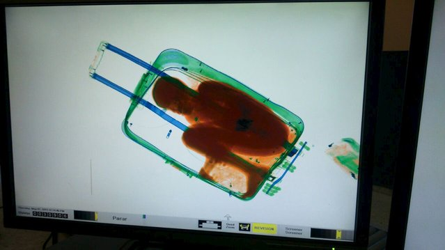 The figure of an eight-year-old boy is seen inside a suitcase on a Spanish civil guard scanner screen at the border between Morocco and Spain's north african enclave Ceuta, Spain in this handout photo released May 8, 2015. A 19-year-old woman was arrested May 7, 2015 for the attempted smuggling of the boy, who was checked by medics and handed over to juvenile prosecutors office, according to authorities. (Photo by Reuters/Ministerio Del Interior)