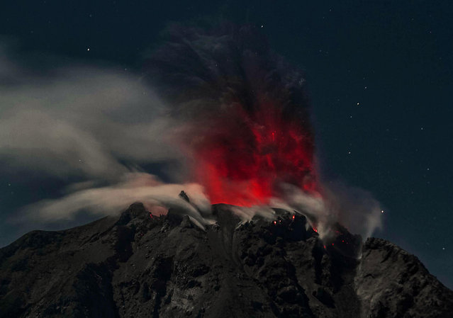 In this timed-exposure night photo taken early on February 12, 2017, Mount Sinabung volcano spews reddish smoke and ash, as seen from the Karo district in North Sumatra province. Activity levels have increased in the past week, with Sinabung shooting hot ash clouds into the sky dozens of times, according to the local volcano monitoring agency. (Photo by AFP Photo/Stringer)
