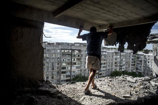A man inspects damaged building in the Mirny district of Luhansk. (Photo by Valery Melnikov/Reuters/Rossiya Segodnya/Courtesy of World Press Photo Foundation)