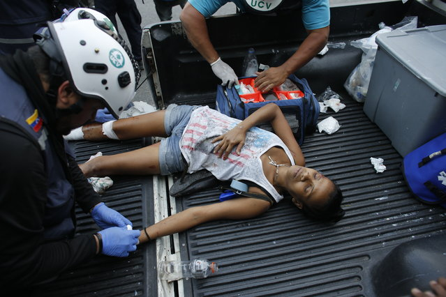A protester who was injured during clashes with security forces is treated in the Altamira neighborhood of Caracas, Venezuela, Wednesday, May 1, 2019. (Photo by Ariana Cubillos/AP Photo)