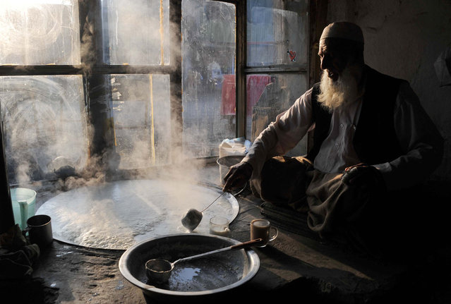An Afghan shopkeeper boils milk as he waits for customers at dawn in Jalalabad, Nangarhar province on February 28, 2014. (Photo by Noorullah Shirzada/AFP Photo)