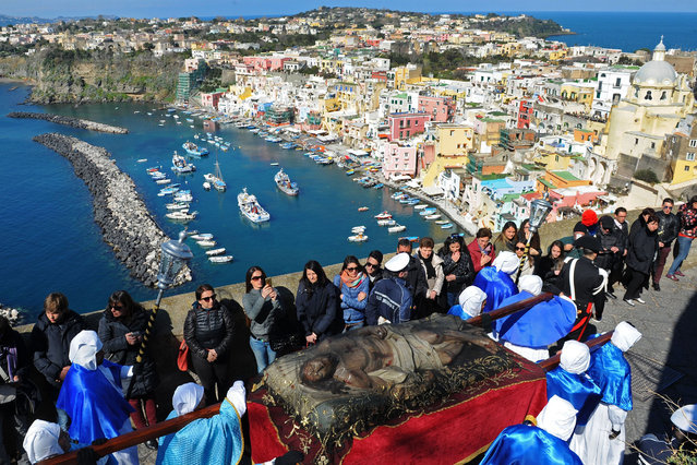Penitents carry a woodden statue of  Jesus Christ  made by Italian sculptor Carmine Lantriceni in 1728 BC, during a procession for  Good Friday  on March 24, 2016 in the small island of Procida in the Gulf of Naples. Christian believers around the world mark the Holy Week of Easter in celebration of the crucifixion and resurrection of Jesus Christ. (Photo by Mario Laporta/AFP Photo)