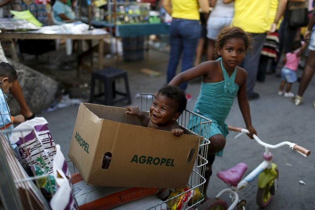 Children wait for their mother at a street market in Mare slum in Rio de Janeiro May 9, 2015. (Photo by Pilar Olivares/Reuters)