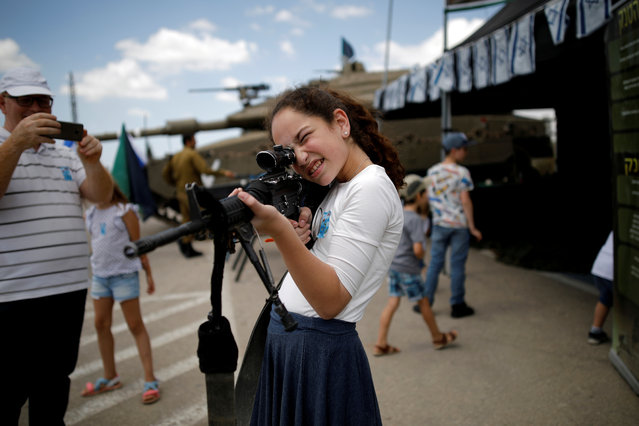 A girl plays with a rifle after a Memorial Day ceremony for the Fallen soldier at Latrun's armoured corps memorial site, Israel on May 8, 2019. (Photo by Corinna Kern/Reuters)