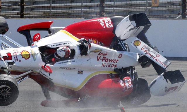 The car driven by Helio Castroneves, of Brazil, lands on the track after flipping after hitting the wall in the first turn during practice for the Indianapolis 500 auto race at Indianapolis Motor Speedway in Indianapolis, Wednesday, May 13, 2015. (Photo by Tom Hemmer/AP Photo)