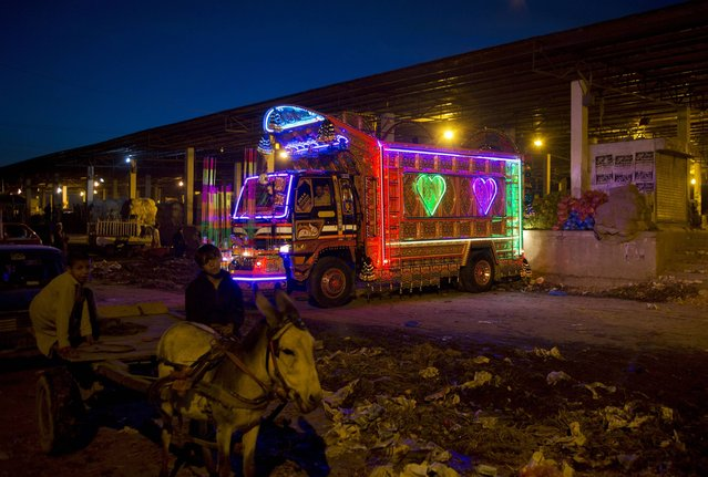 A truck decorated with florescent lights offloads vegetables and fruits at a wholesale market in Islamabad, Pakistan, on Wednesday, March 19, 2014. Owners of such trucks spend much money on decorating their vehicles in Pakistan. (Photo by B. K. Banagsh/AP Photo)