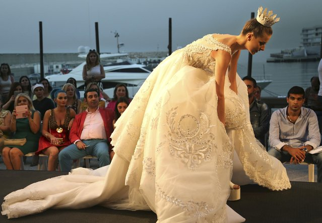 A model tries to fix her dress for walking as she displays a wedding dress by the Emirati designer Mona al-Mansouri of her Spring-Summer 2015 fashion show during the summer fashion week at Saint George Yacht Club in Beirut, Lebanon, Tuesday, May 19, 2015. (Photo by Hussein Malla/AP Photo)