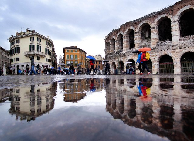 Tourists walk in the pouring rain along the old arena, right, and buildings of the old town in Verona, Italy, Tuesday, April 23, 2019. (Photo by Michael Probst/AP Photo)