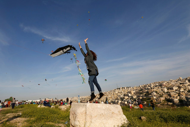 A woman prepares to fly a kite, during an event celebrating spring at the Citadel in Amman, Jordan, April 15, 2016. (Photo by Muhammad Hamed/Reuters)