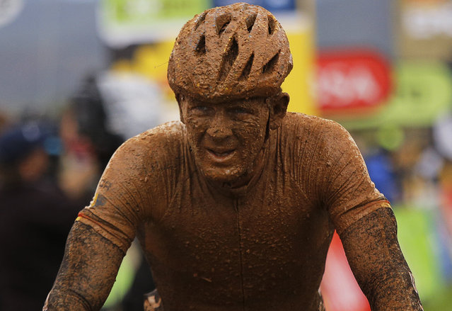 """German rider Karl Platt from Bulls Racing is covered in mud after heavy overnight rain turned the trail into mud during stage 2 of the annual ABSA Cape Epic mountain bike stage race in Cape Town, South Africa, March 25, 2014. The multi day stage race is known as the """"Tour de France"""" of mountain biking and sees 1,200 competitors riding 720km in seven days. The race includes the worlds leading professional racers along with amateur cyclists. (Photo by Kim Ludbrook/EPA)"""