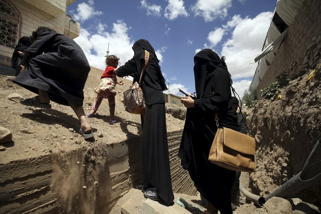 Women walk out of an underground water tunnel with other displaced people after they were forced to flee their home due to ongoing air-strikes carried out by the Saudi-led coalition in Sanaa May 2, 2015. (Photo by Mohamed al-Sayaghi/Reuters)