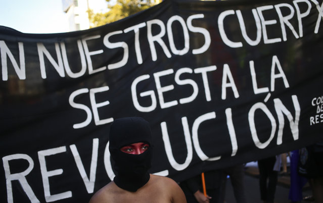 "A masked woman walks in front of a banner that says in Spanish: ""The revolution gestates in our bodies"" at a march marking International Women's Day outside La Moneda presidential palace in Santiago, Chile, Wednesday, March 8, 2017. Many women stayed home from work, joined rallies or wore red Wednesday as International Women's Day was observed with a multitude of events around the world. (Photo by Esteban Felix/AP Photo)"