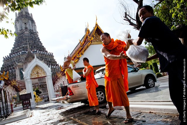 Thai monks unload sandbags to help fortify a temple from rising flood waters from the overflowing Chao Phraya river