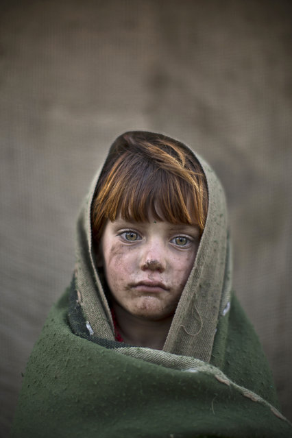 In this Friday, January 24, 2014 photo, Afghan refugee girl, laiba Hazrat, 6, poses for a picture, while playing with other children in a slum on the outskirts of Islamabad, Pakistan. (Photo by Muhammed Muheisen/AP Photo)