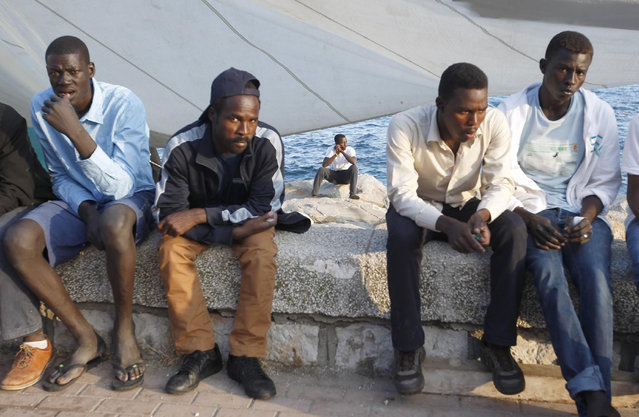 Migrants sit at the Franco-Italian border in Ventimiglia, Italy, Wednesday, June 17, 2015. European Union nations failed to bridge differences Tuesday over an emergency plan to share the burden of the thousands of refugees crossing the Mediterranean Sea, while on the French-Italian border, police in riot gear forcibly removed dozens of migrants. (AP Photo/Lionel Cironneau)