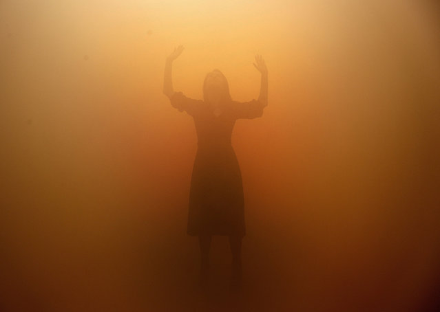 """A visitor tries to orientate through a room full of fog called """"Your blind passenger"""" as part of the exhibition Olafur Eliasson: """"In real life"""" at the Tate Modern Gallery in London, Tuesday, July 9, 2019. The Tate Modern has brought together around 40 works of Eliasson spanning the last three decades, and are on display from July 11, 2019 until January 5, 2020. (Photo by Frank Augstein/AP Photo)"""