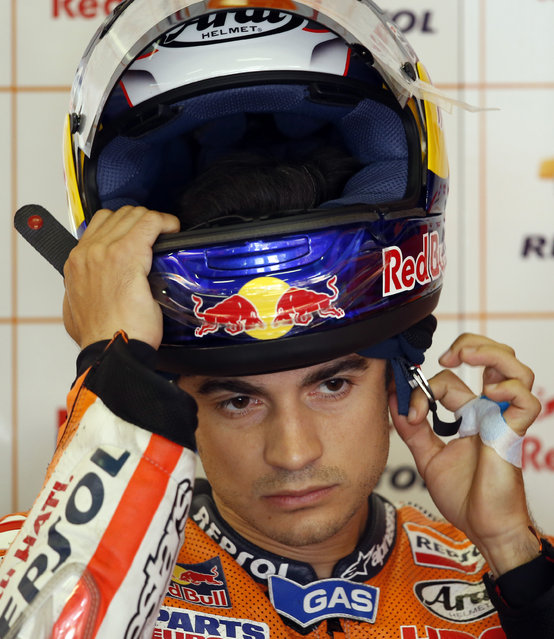 Spanish Moto GP rider Dani Pedrosa adjusts his helmet in his box before the third free practice for the motorcycle GP in Montmelo, Spain, Saturday, June 13, 2015. The Catalunya Grand Prix will take place on Sunday in Montmelo. (AP Photo/Manu Fernandez)